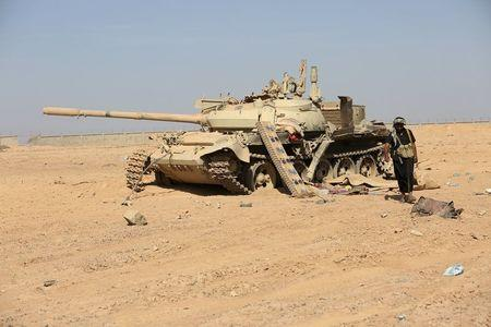 A tribesman loyal to Yemen's President Abd-Rabbu Mansour Hadi walks past a damaged tank at the Mass army barracks after the pro-Hadi forces took it from Houthi rebels in the country's northwestern province of Marib December 18, 2015. REUTERS/Ali Owidha