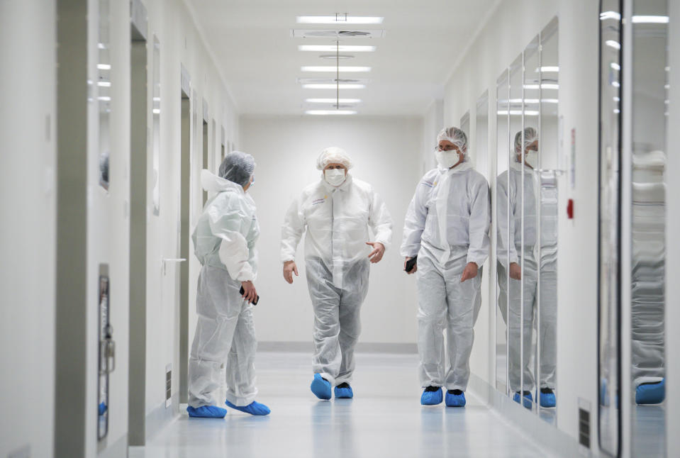 Britain's Prime Minister Boris Johnson, centre, dressed in protective gear is guided during a visit to the AstraZeneca facility in Macclesfield, England, on Tuesday April 6, 2021, to learn more about their dollars 500 million investment into the site. Johnson said Monday that Britain's vaccination program is going well and infections are falling, confirming that many shops and businesses will be allowed to reopen next week. (Dave Thompson/Pool via AP)