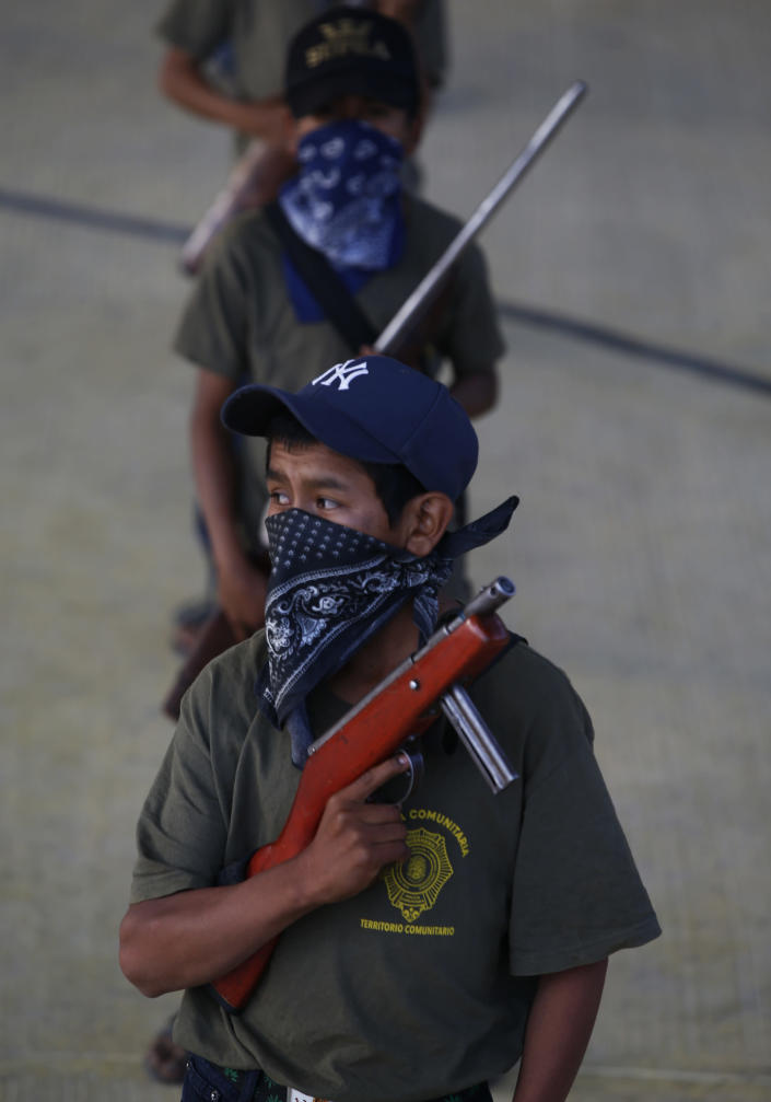 Children practice with weapons, some real and some fake, during a display for the media designed to attract the federal government's attention to the dangers of organized crime their town negotiates daily in Ayahualtempa, Guerrero state, Mexico, Wednesday, April 28, 2021. In Ayahualtempa, they plan to keep displaying armed children until they feel safe. (AP Photo/Marco Ugarte)