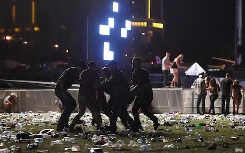 <span>A wounded concert-goer is carried from the scene</span> <span>Credit: David Becker/Getty </span>