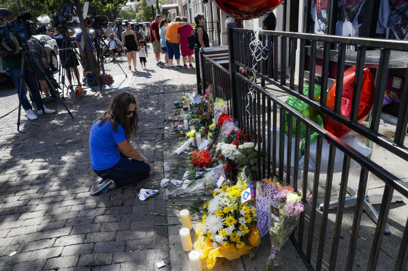 """A mourner kneels at a makeshift memorial near a members of the media outside the """"Hole in the Wall"""" bar in the Oregon District, Monday, Aug. 5, 2019, in Dayton, Ohio. The area was the scene of a mass shooting the previous day. (AP Photo/John Minchillo)"""