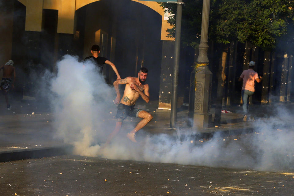 Anti-government protesters run amid tear gas fired by riot police during a protest marking the first anniversary of the massive blast at Beirut's port, near Parliament Square, In Beirut, Lebanon, Wednesday, Aug. 4, 2021. United in grief and anger, families of the victims and other Lebanese came out into the streets of Beirut on Wednesday to demand accountability as banks, businesses and government offices shuttered to mark one year since the horrific explosion. (AP Photo/Bilal Hussein)
