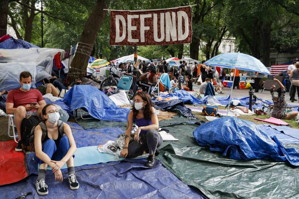 """Protesters gather under a sign reading """"DEFUND"""" at an encampment outside City Hall, Tuesday, June 30, 2020, in New York. City Council members were due to debate and vote Tuesday night on a plan to shift $1 billion from policing to education and social services, with time running short ahead of the fiscal year that begins Wednesday. (AP Photo/John Minchillo)"""