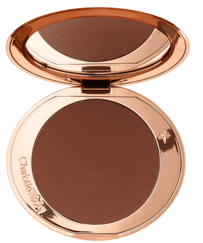 """<p><strong>Charlotte Tilbury</strong></p><p>nordstrom.com</p><p><strong>$55.00</strong></p><p><a href=""""https://go.redirectingat.com?id=74968X1596630&url=https%3A%2F%2Fwww.nordstrom.com%2Fs%2Fcharlotte-tilbury-airbrush-flawless-finish-bronzing-powder%2F5581046&sref=https%3A%2F%2Fwww.goodhousekeeping.com%2Fbeauty-products%2Fg36020083%2Fbest-bronzer-for-dark-skin%2F"""" rel=""""nofollow noopener"""" target=""""_blank"""" data-ylk=""""slk:Shop Now"""" class=""""link rapid-noclick-resp"""">Shop Now</a></p><p>This oversized Charlotte Tilbury compact holds an ample amount of product, and the bronzer accentuates a warm complexion on dark skin tones. The formula is finely-milled and <strong>blends into your skin seamlessly, leaving you with a flawless </strong><strong><a href=""""https://www.goodhousekeeping.com/beauty/makeup/g32984720/best-airbrush-makeup/"""" rel=""""nofollow noopener"""" target=""""_blank"""" data-ylk=""""slk:airbrush finish"""" class=""""link rapid-noclick-resp"""">airbrush finish</a>.</strong> It also contains hyaluronic acid, which locks moisture into your skin. </p>"""