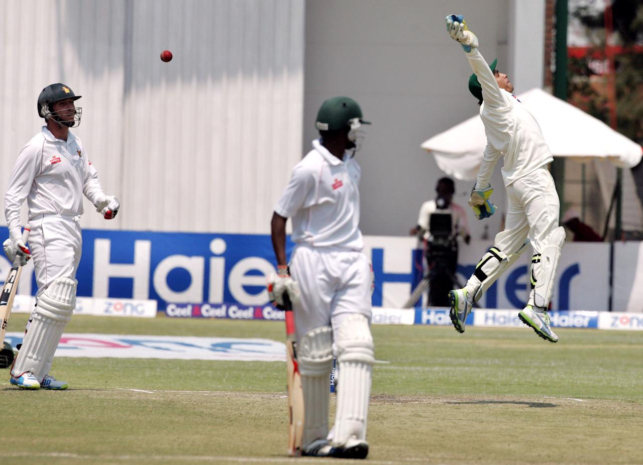 Pakistan's wicket keeper Adnan Akmal (R) leaps for a throw in as Zimbabwe's captain Brendan Taylor (L) looks on during the fourth day of the second test match between Pakistan and Zimbabwe at the Harare Sports Club September 13, 2013.   AFP PHOTO / JEKESAI NJIKIZANA        (Photo credit should read JEKESAI NJIKIZANA/AFP/Getty Images)