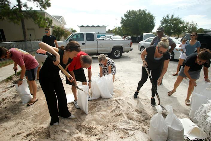 Residents work together to fill sandbags for each other at Bobby Hicks Park as residents prepare ahead of Hurricane Irma on September 5, 2017 in Tampa, Florida.