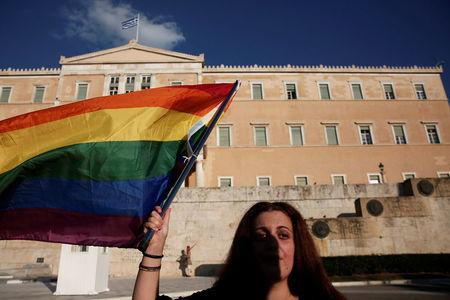 A protester waves a rainbow flag during a demonstration as the Greek Parliament debates bill allowing people to choose legal gender, in Athens, Greece, October 9, 2017. REUTERS/Alkis Konstantinidis