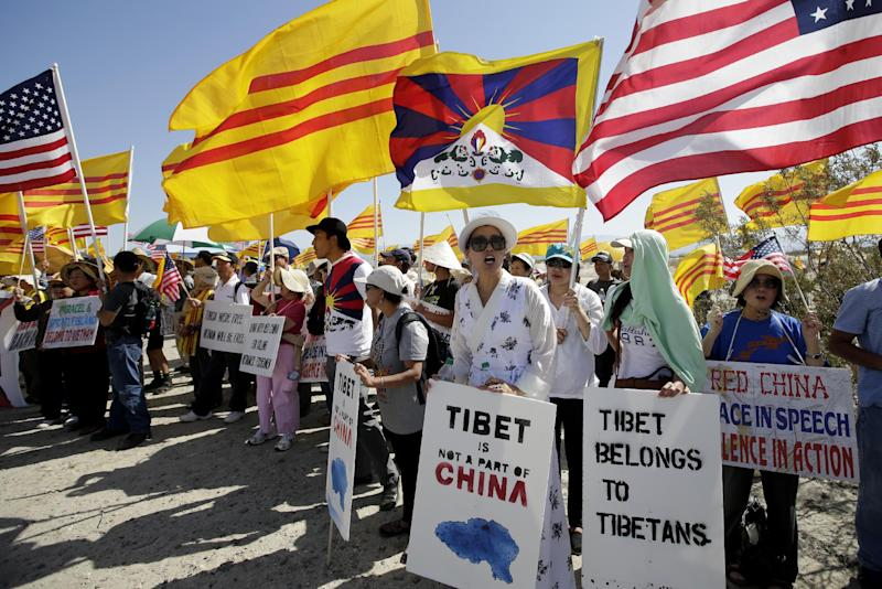 Protesters chant slogans near the Annenberg Retreat at Sunnylands in Rancho Mirage, Calif., Saturday, June 8, 2013, where President Barack Obama and Chinese President Xi Jinping, not shown, are wrapping up a two-day summit. (AP Photo/Jae C. Hong)