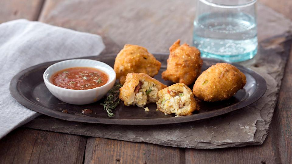 """<p>Hopefully your candidate's poll numbers don't dip as much as you'll be dipping these fritters into the homemade bacon pepper sauce. Similar to hush puppies, a <a href=""""https://www.thedailymeal.com/cook/classic-southern-recipes-are-better-grandma-s-gallery?referrer=yahoo&category=beauty_food&include_utm=1&utm_medium=referral&utm_source=yahoo&utm_campaign=feed"""" rel=""""nofollow noopener"""" target=""""_blank"""" data-ylk=""""slk:classic Southern dish"""" class=""""link rapid-noclick-resp"""">classic Southern dish</a>, this appetizer gets its rich flavor from whole kernels of hominy and thyme. </p> <p><a href=""""https://www.thedailymeal.com/recipes/hominy-fritters-bacon-thyme-dipping-sauce-recipe?referrer=yahoo&category=beauty_food&include_utm=1&utm_medium=referral&utm_source=yahoo&utm_campaign=feed"""" rel=""""nofollow noopener"""" target=""""_blank"""" data-ylk=""""slk:For the Hominy Fritters recipe, click here."""" class=""""link rapid-noclick-resp"""">For the Hominy Fritters recipe, click here.</a></p>"""