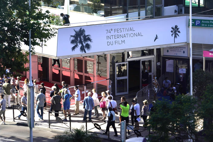 Members of the public walk in front of the Palais des Festival prior to the 74th international film festival, Cannes, southern France, July 5, 2021. The Cannes film festival runs from July 6 - July 17, 2021. (AP Photo/ Brynn Anderson)