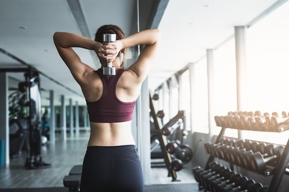 Fitness woman lifting dumbbell at gym.