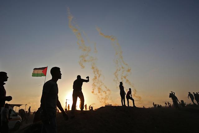 <p>Palestinians protest as tear gas fumes erupt near the border with Israel east of Khan Yunis in the southern Gaza Strip on May 15, 2018 marking 70th anniversary of Nakba — also known as Day of the Catastrophe in 1948 — and against the U.S. relocation of its embassy from Tel Aviv to Jerusalem. (Photo: Said Khatib/AFP/Getty Images) </p>