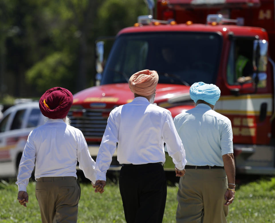 Men walk near the Sikh Temple of Wisconsin in Oak Creek, Wis, after a shooting took place, Sunday, Aug 5, 2012. (AP Photo/Jeffrey Phelps)