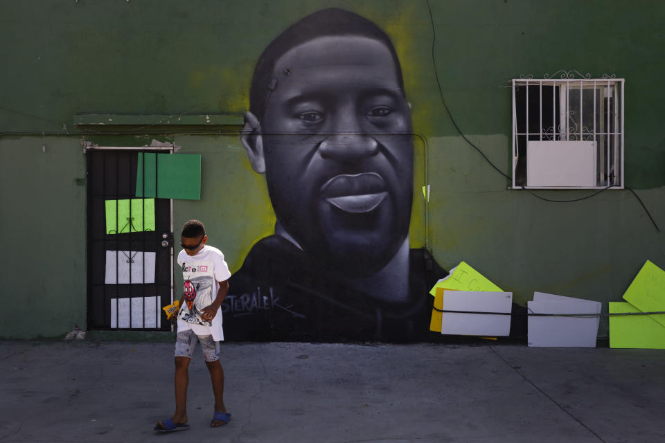 Benjamin Jackson III, 10, walks past a mural depicting George Floyd in the Watts neighborhood of Los Angeles, Tuesday, June 9, 2020. There were no fires this time in Watts. There was no looting, no shooting and no National Guard troops patrolling the streets. When protesters around the country began demanding racial justice over the Minneapolis police killing of George Floyd, there may have been mentions of Watts and faint echoes of the riots that broke out in the Los Angeles neighborhood 55 years ago. But they didn't happen there. (AP Photo/Jae C. Hong)