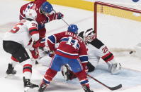 Montreal Canadiens' Nick Suzuki (14) scores past New Jersey Devils goaltender Mackenzie Blackwood as Devils' Mirco Mueller (25) and Canadiens' Brendan Gallagher (11) look for a rebound during the second period of an NHL hockey game in Montreal, Saturday, Nov. 16, 2019. (Graham Hughes/The Canadian Press via AP)