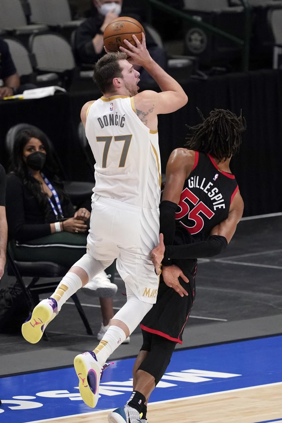 Dallas Mavericks guard Luka Doncic (77) is fouled by Toronto Raptors forward Freddie Gillespie (55) on a three-point shot attempt in the second half of an NBA basketball game in Dallas, Friday, May 14, 2021. (AP Photo/Tony Gutierrez)