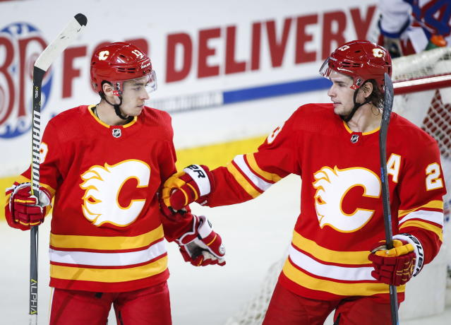 Calgary Flames' Johnny Gaudreau, left, celebrate his goal with teammate Sean Monahan during the first period of an NHL hockey game against the New York Rangers in Calgary, Alberta, Friday, March 15, 2019. (Jeff McIntosh/The Canadian Press via AP)