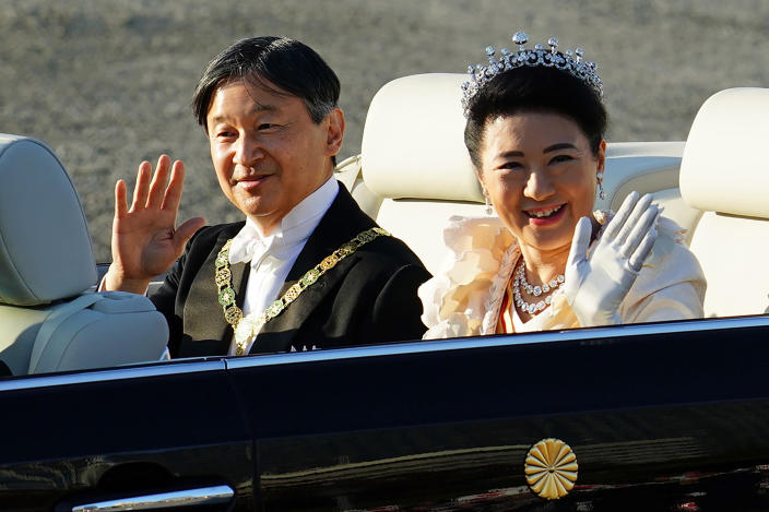 Japanese Emperor Naruhito, left, and Empress Masako, right, wave during the royal motorcade in Tokyo, Sunday, Nov. 10, 2019. (AP Photo/Eugene Hoshiko)