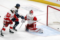 Columbus Blue Jackets forward Kevin Stenlund, center, watches a goal by teammate Gavin Bayreuther (not shown) between Detroit Red Wings defenseman Troy Stecher, left, and goalie Thomas Greiss during the first period an NHL hockey game in Columbus, Ohio, Friday, May 7, 2021. (AP Photo/Paul Vernon)