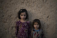 Zahra, 6, and Adina, 5, pose for a photo outside their home at a village in Wardak province, Afghanistan, Monday, Oct. 11, 2021. (AP Photo/Felipe Dana)