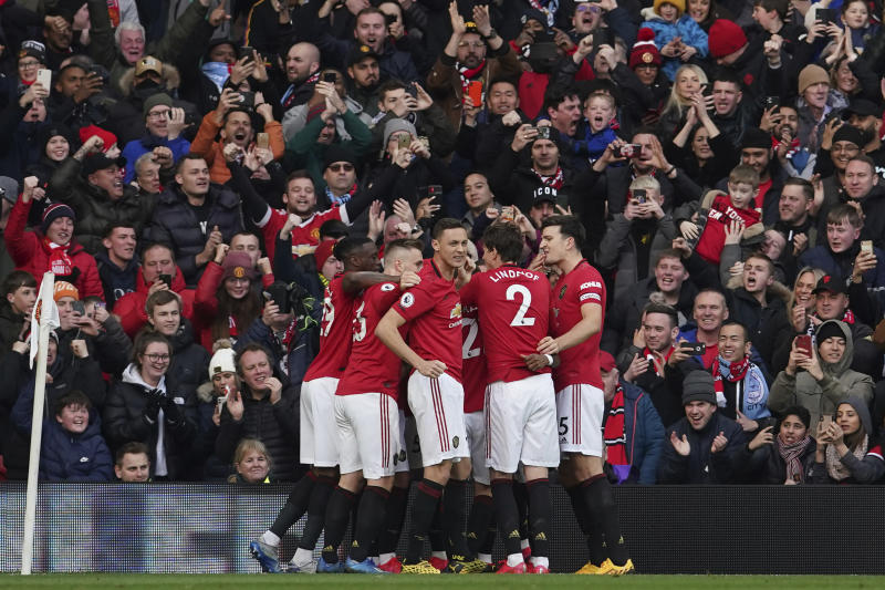 Manchester United's team players celebrate after Anthony Martial scored the opening goal during the English Premier League soccer match between Manchester United and Manchester City at Old Trafford in Manchester, England, Sunday, March 8, 2020. (AP Photo/Dave Thompson)