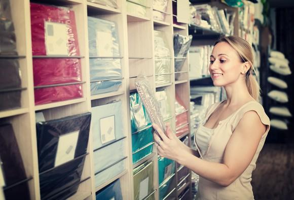Woman looking at bed linens.