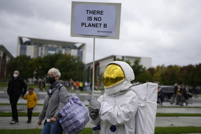 An activist holds a banner during a Fridays for Future global climate strike in Berlin, Germany, Friday, Sept. 24, 2021. (AP Photo/Markus Schreiber)