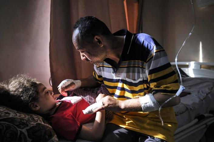 Palestinian Ryad Eshkuntana, checks his daughter Suzy, as they receive medical care at Al-Shifa hospital in Gaza City, on May 19, 2021, after his wife and other children were killed in an Israeli air strike. - Deafening air strikes and rocket fire once more shook Gaza overnight and early today amid an international diplomatic push to broker a ceasefire after more than a week of bloodshed. (Photo by MAHMUD HAMS / AFP) (Photo by MAHMUD HAMS/AFP via Getty Images)