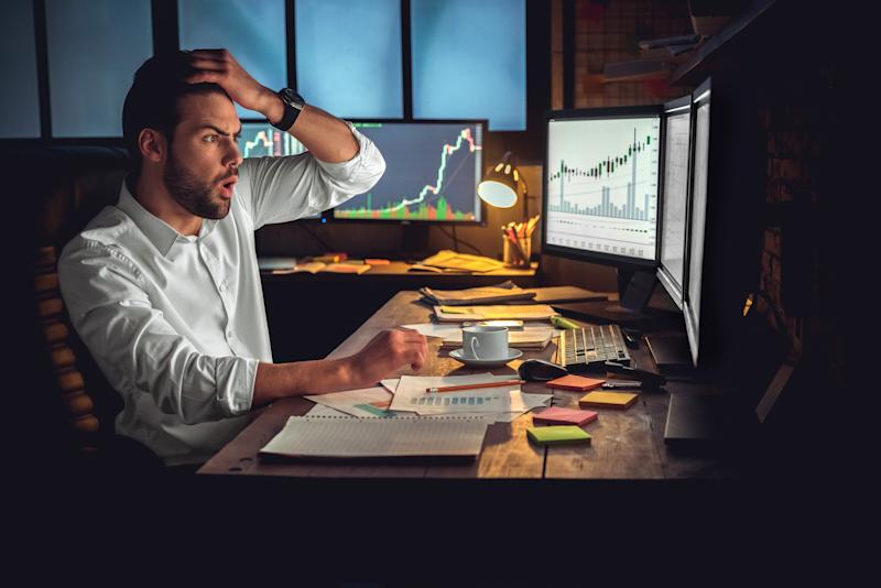 A worried person looks at stock charts on a computer screen.