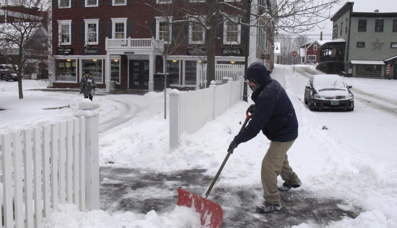 Bill Langley, of the Green Mountain Inn in Stowe, Vt., shovels snow from a sidewalk on Tuesday, Nov. 12, 2019. In the first significant snow of the season a wintry mix swept into northern New England, with hundreds of schools closed or delayed in Vermont due to snow, and slick conditions in New Hampshire and Maine. The National Weather Service says record cold could follow the snow. (AP Photo/Wilson Ring)