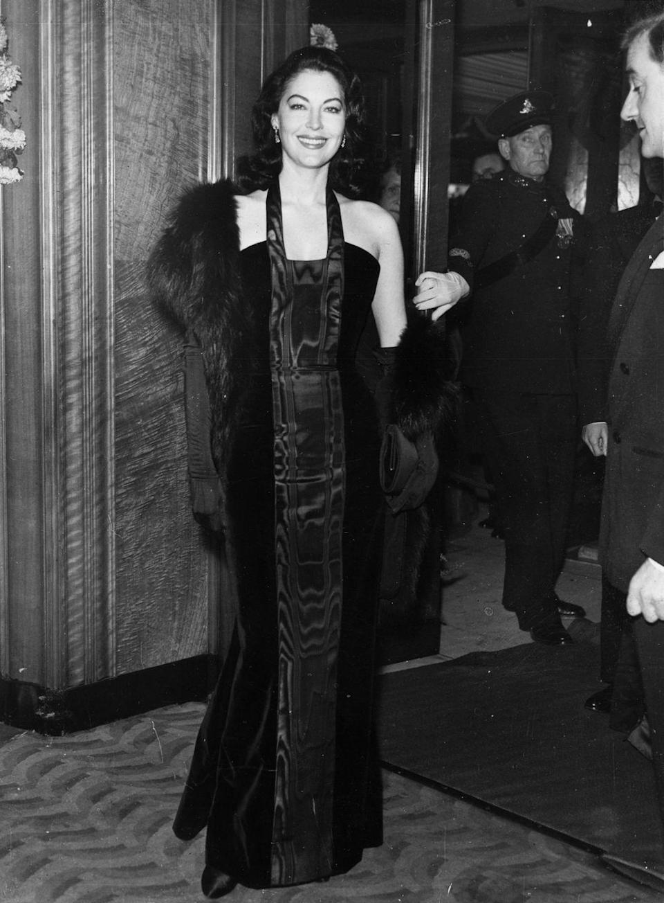 <p>Gardner stuns in a black sheath evening dress boasting a moiré-like pattern and a fur wrap while attending a Royal Film Premiere. </p>