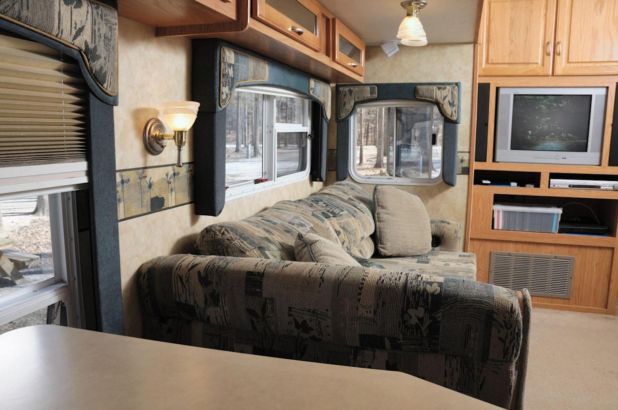 Living room in rv trailer in campground with TV on