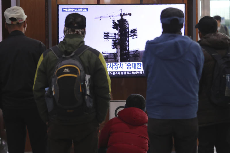 """People watch a TV screen showing a file image of the North Korean long-range rocket at a launch pad during a news program at the Seoul Railway Station in Seoul, South Korea, Monday, Dec. 9, 2019. North Korea said Sunday it carried out a """"very important test"""" at its long-range rocket launch site that it reportedly rebuilt after having partially dismantled it after entering denuclearization talks with the United States last year. (AP Photo/Ahn Young-joon)"""