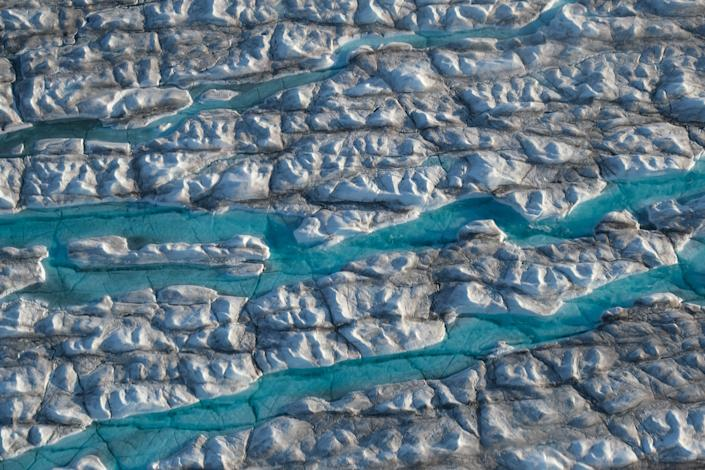 ILULISSAT, GREENLAND - AUGUST 04: In this view from an airplane rivers of meltwater carve into the Greenland ice sheet near Sermeq Avangnardleq glacier on August 04, 2019 near Ilulissat, Greenland. The Sahara heat wave that recently sent temperatures to record levels in parts of Europe has also reached Greenland. Climate change is having a profound effect in Greenland, where over the last several decades summers have become longer and the rate that glaciers and the Greenland ice cap are retreating has accelerated.   (Photo by Sean Gallup/Getty Images)