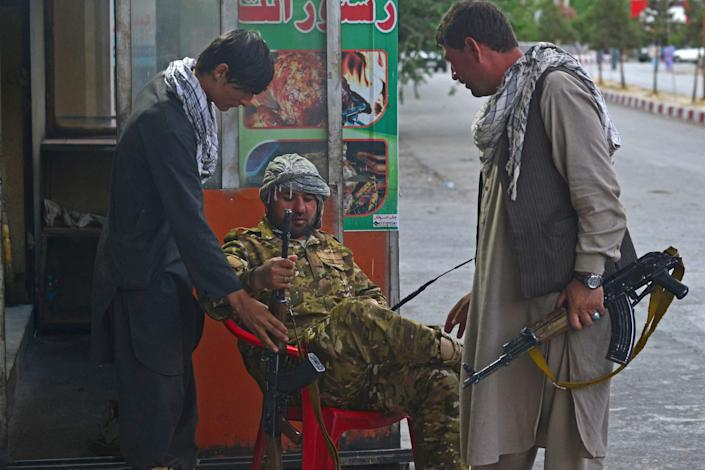 Members of Afghan security forces guard along the roadside in Panjshir province on August 14, 2021.