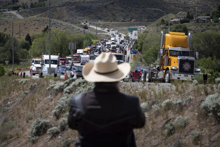 A man watches a convoy of truckers and other vehicles travel on Hwy 5 in support of the Tk'emlups te Secwepemc people after the remains of 215 children were discovered buried near the former Kamloops Indian Residential School, in Kamloops, British Columbia, on Saturday, June 5, 2021. (Darryl Dyck/The Canadian Press via AP)