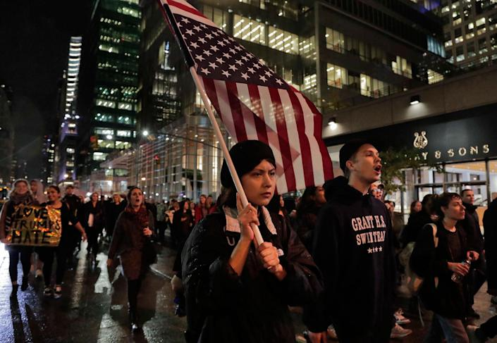 <p>A protester carries an upside down American flag as she walks along Sixth Avenue while demonstrating against President-elect Donald Trump, Wednesday, Nov. 9, 2016, in New York. Thousands of protesters around the country took to the streets Wednesday to condemn the election of Trump as president. (Photo: Julie Jacobson/AP) </p>