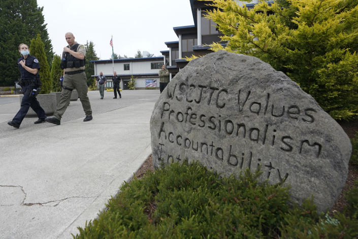 """Cadets LeAnne Cone, left, of the Vancouver Police Dept., and Kevin Burton-Crow, right, of the Thurston Co. Sheriff's Dept., walk past a rock at the Washington state Criminal Justice Training Commission engraved with """"WSCJTC Values Professionalism, Accountability Integrity,"""" on the way to a training exercise Wednesday, July 14, 2021, in Burien, Wash. Washington state is embarking on a massive experiment in police reform and accountability following the racial justice protests that erupted after George Floyd's murder last year, with nearly a dozen new laws that took effect Sunday, July 25, but law enforcement officials remain uncertain about what they require in how officers might respond — or not respond — to certain situations, including active crime scenes and mental health crises. (AP Photo/Ted S. Warren)"""