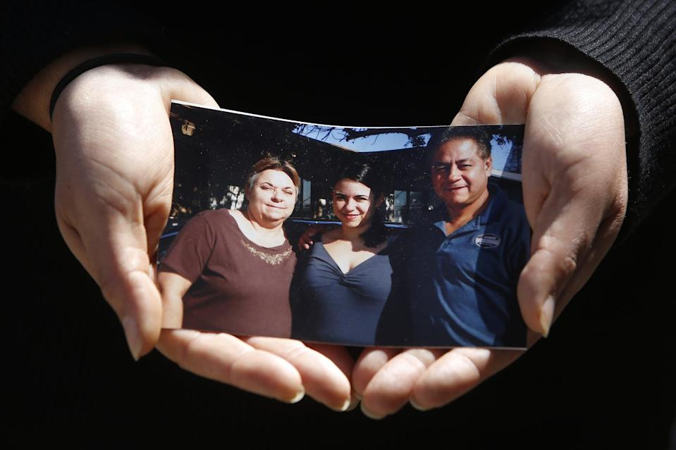 SAN FRANCISCO, CA - AUGUST 20: Kristin Urquiza holds a photo of herself (center) with her father Mark Urquiza (right) and mother Brenda Urquiza (left) as she stands for a portrait on Thursday, August 20, 2020 in San Francisco, Calif.  Kristin Urquiza, a San Francisco environmentalist, gave a speech at the Democratic National Convention about her dad's death from COVID-19.