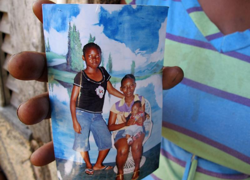 Beverly Kennedy holds an old photograph of her slain daughter, Nicketa Cameron, standing left, in the Denham Town slum in Kingston, Jamaica, Thursday March 8, 2012. Cameron, 13, was standing by a washing machine in a narrow hallway facing the street when she was killed Monday by a bullet to the head during a roughly 40-minute gun battle between police and criminals. The family insists the bullets were fired into their home by police. (AP Photo/David McFadden)