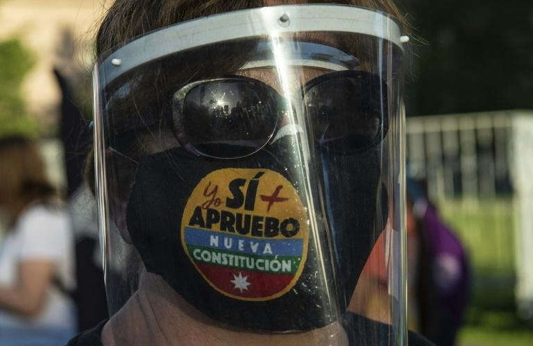 A woman with a face mask reading 'Yes, I do approve the new constitution' takes part in a rally in support of amending the charter established under the military rule of General Augusto Pinochet