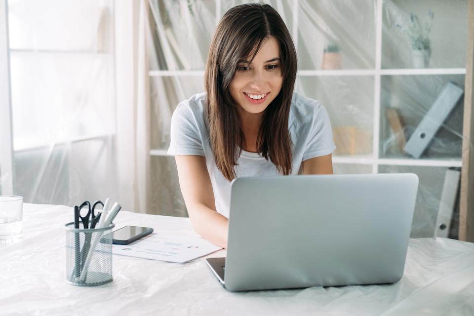 Freelancer lifestyle. Home relocation. Remote job. Virtual office. Happy satisfied woman working online using laptop in new modern light room with covered furniture.