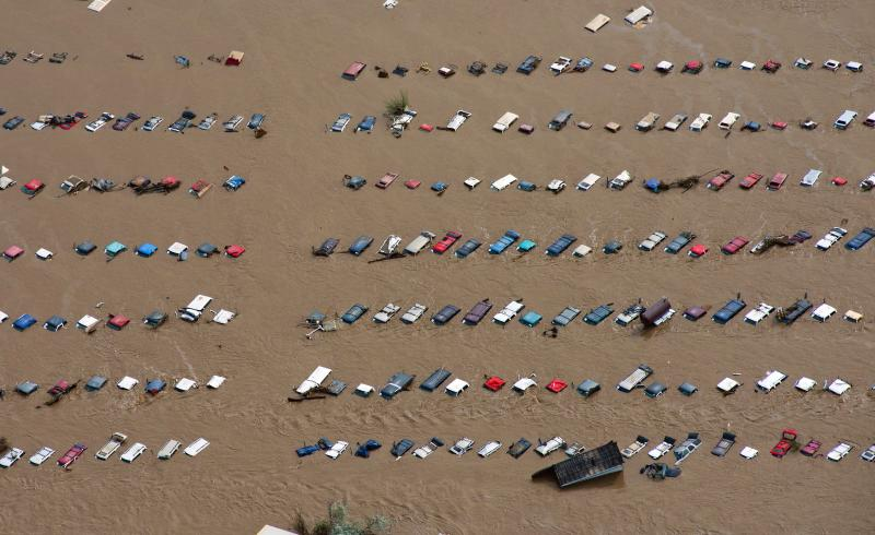 FILE - In this Saturday, Sept. 14, 2013 file photo, a field of parked cars and trucks sits partially submerged near Greeley, Colo., as debris-filled rivers flooded into towns and farms miles from the Rockies. On Wednesday, Jan. 14, 2014, scientists from National Oceanic and Atmospheric Administration say 2013 was the wettest year for the continental U.S. since 2009. The average rainfall totaled 31 inches, 2 inches above the previous century's average. (AP Photo/John Wark)