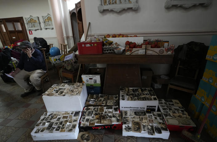 A resident makes a mobile phone call as he sits in front of historical photographs rescued from flood waters at the local church, converted in a flood victims aide center, in Trooz, Belgium, Tuesday, July 27, 2021. Uncontrollable water destroyed approximately half of the homes in the small village of Trooz, leaving tons of debris in its wake in one of the most violent natural disasters to hit Belgium in a century. (AP Photo/Virginia Mayo)