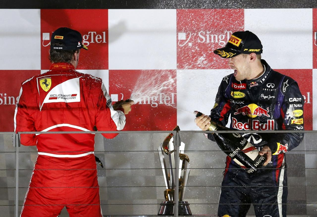 Ferrari Formula One driver Fernando Alonso of Spain (L) and Red Bull Formula One driver Sebastian Vettel of Germany celebrate with champagne on the podium after the Singapore F1 Grand Prix at the Marina Bay street circuit in Singapore September 22, 2013. Vettel cruised to a third straight Singapore Grand Prix victory on Sunday and moved closer to a fourth consecutive Formula One world title with a dominant drive under the floodlights at the Marina Bay Street Circuit. REUTERS/Edgar Su (SINGAPORE - Tags: SPORT MOTORSPORT F1 TPX IMAGES OF THE DAY)