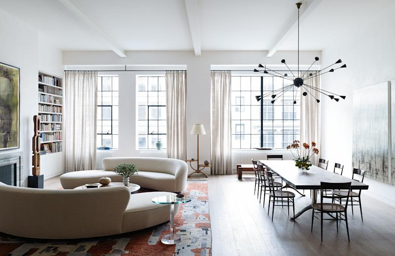 The open space at the front of designer Laura Santos's SoHo loft comprises two Cloud sofas by Vladimir Kagan from Ralph Pucci. The coffee table is by Ado Chale, designed in Belgium in 1970 and purchased from Van den Akker Antiques. The side table is by Les Prismatiques, designed in France in the 1960s and purchased from Wyeth. The standing sculpture is attributed to Leo Amino and designed in 1950 and also purchased from Wyeth. The floor lamp is French, 1940s and from the Wooster Gallery, while the rug is from Woven Accents. The loft's drapes are custom, with material from Calvin Fabrics.