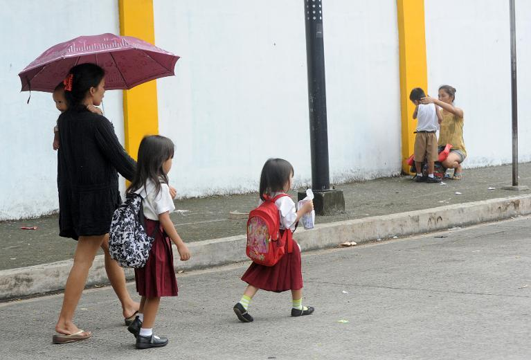 Parents bring their children to an elementary school in Manila on July 4, 2012