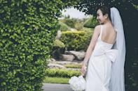 <p>Have your photographer stand behind you and go for a casual lean, letting your bouquet hang down to the side and trace your shape.</p>