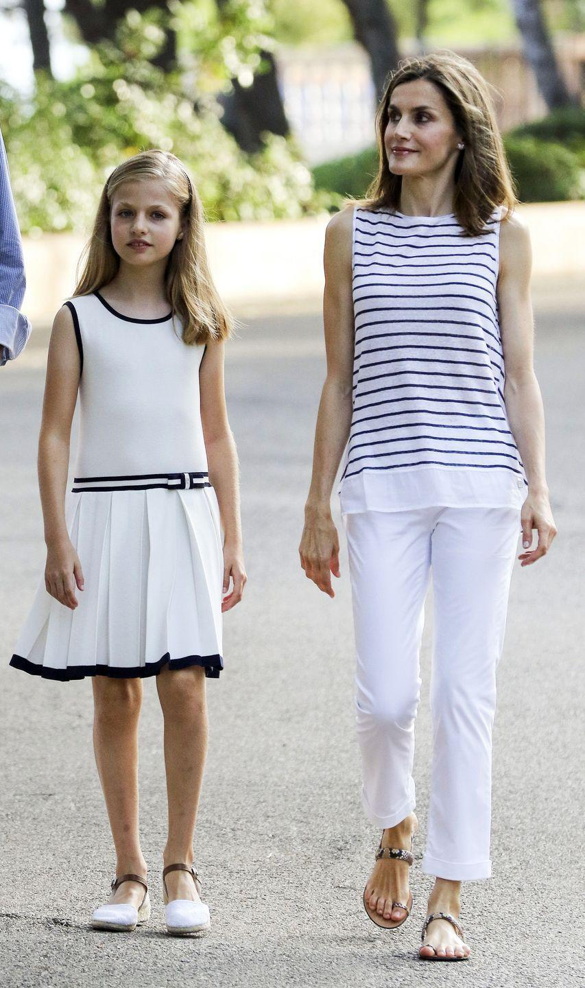 <p>Queen Letizia does European casual well, too–here she is in summery white pants and a striped white and navy top with her daughter, Princess Leonor. </p>