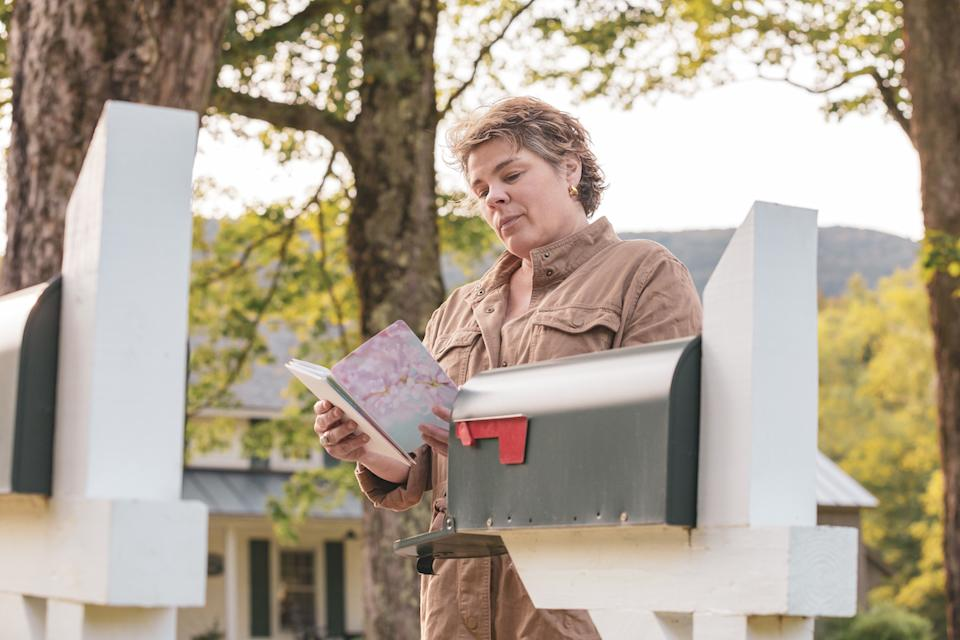 middle aged white woman Woman Reading a greeting card at the mailbox